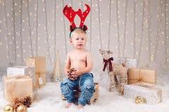 有鹿麋垫铁头饰带的白种人孩子庆祝圣诞节或新年的 库存图片