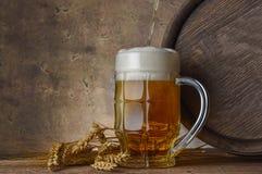有麦子耳朵的啤酒杯和在黑暗的墙壁背景的木桶,倒啤酒 免版税库存图片