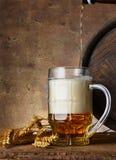 有麦子耳朵的啤酒杯和在黑暗的墙壁背景的木桶,倒啤酒 库存照片