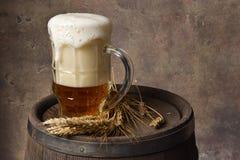 有麦子耳朵的啤酒杯在黑暗的墙壁背景的木桶 免版税库存照片