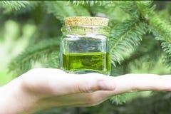 有黄柏盖帽的玻璃瓶是半满的与绿色黄色油用花蜜 库存照片