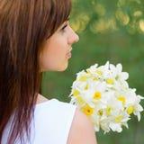 有黄水仙花束的美丽的女孩在白色礼服的 免版税库存图片