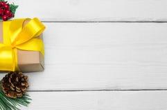 有黄色丝带弓的在白色木葡萄酒背景的礼物盒和锥体 图库摄影
