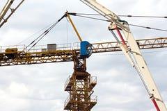 有黄色伸缩臂架的流动建筑用起重机和在白色云彩和深蓝天的大塔吊在背景,重 免版税库存照片