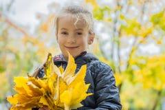 有黄色叶子的俏丽的女孩 免版税库存照片