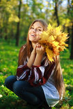 有黄色叶子的笑的女孩 库存照片