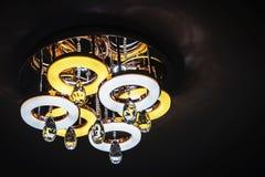 有黄色和白色圈子的枝形吊灯在黑暗的背景 免版税库存照片