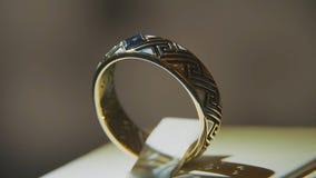 有黄色宝石的金黄戒指 敲响在与青玉browm,婚戒-与金刚石的jewelery的金子 免版税库存照片