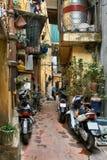 有黄色房子和停放的摩托车的美丽如画的亚洲城市街道 免版税库存照片