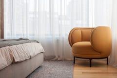 有黄色扶手椅子的现代客厅以站立在床旁边的窗口为背景 免版税库存图片