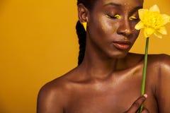 有黄色构成的快乐的年轻非洲妇女在她的眼睛 反对黄色背景的女性模型与黄色花 免版税库存照片