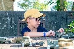 有黄色盖帽的小男孩使用与外面玩具 免版税库存照片