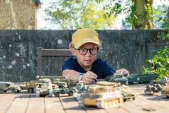 有黄色盖帽的小男孩使用与外面玩具 免版税图库摄影