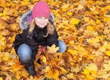 有黄色秋叶的小白肤金发的女孩 免版税库存图片