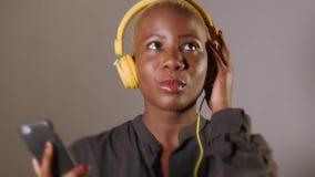 有黄色耳机和手机的年轻愉快和可爱的美国黑人的妇女听互联网音乐歌曲微笑的 股票视频