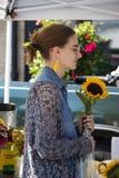 有黄色耳环的女孩和denium女衬衫和玻璃拿着一个向日葵在樱桃街道农夫市场上 图库摄影