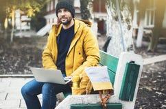 有黄色背包的,夹克,盖帽,热杯子饮料咖啡行家,自由职业者使用在秋天街道的计算机开放膝上型计算机 免版税库存照片