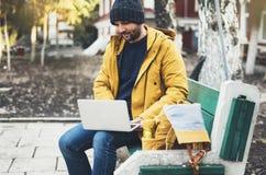 有黄色背包的,夹克,盖帽,热杯子饮料咖啡行家,自由职业者使用在秋天街道的计算机开放膝上型计算机 免版税图库摄影
