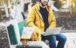 有黄色背包的,夹克,盖帽,热杯子饮料咖啡行家,自由职业者使用在秋天街道的计算机开放膝上型计算机 库存图片
