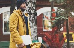 有黄色背包的,夹克,盖帽,热水瓶咖啡行家藏品在春天街道室外关闭的计算机膝上型计算机 图库摄影