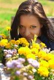 有黄色花的美丽的女孩 免版税库存照片