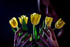 有黄色郁金香的妇女在黑暗的背景 免版税库存照片