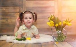 有黄色郁金香花束的一个小孩子  有礼品的一个男孩 库存照片
