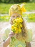 有黄色野花的美丽的女孩 免版税图库摄影