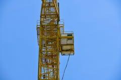有黄色颜色一个长的箭头的高层建筑用起重机反对天空蔚蓝的在混凝土一个新的多层的大厦  免版税图库摄影
