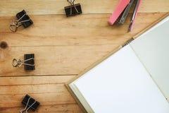有黏合剂夹子和订书机的被打开的笔记本在木桌bac 库存照片