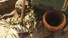 有黏土花盆的老生锈的铁锹在晴朗被放弃的庭院里- 免版税库存图片