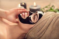 有黑净化黑面具的美女在她的面孔 秀丽有在温泉沙龙的黑面部脱层面具的模型女孩 免版税库存照片