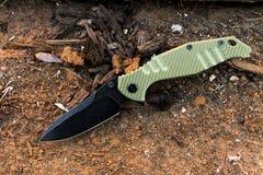 有黑刀片和绿色handl的刀子 老木头 军事 图库摄影