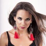 有黑发和侈奢的耳环的美丽的妇女 免版税图库摄影