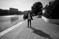 有黑发和眼睛的一个年轻人步行沿着向下街道的 生活方式 高速增长 免版税库存图片