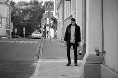 有黑发和眼睛的一个年轻人步行沿着向下街道的 生活方式 高速增长 库存图片