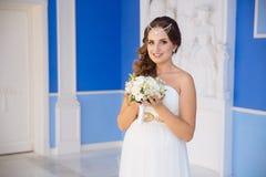 有黑发和装饰品的一个女孩由小珠做成在她的头,穿戴在婚礼礼服,拿着花和 免版税库存图片