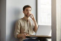 有黑发微笑的美丽的白种人人,坐在有膝上型计算机的自助食堂,谈话在电话和看照相机 图库摄影