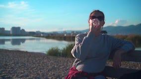 有黑发的一个女孩在运动衫和玻璃坐长凳在海附近并且喝从塑料瓶的水 股票录像