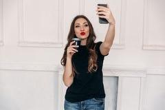 有黑发的一个好女孩有红色明亮的嘴唇的,举行每杯咖啡在她的手上,和送亲吻到照相机  库存照片