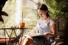 有黑发的一个年轻亭亭玉立的友好的女孩,穿戴在偶然成套装备,坐在桌上并且读在一份舒适咖啡的一本书 免版税图库摄影