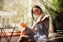 有黑发的一个年轻亭亭玉立的微笑的女孩,穿戴在偶然成套装备,坐在桌上并且喝在一份舒适咖啡的咖啡 库存图片