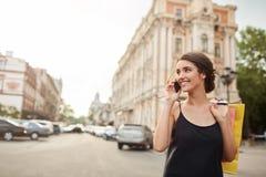 有黑发的在黑礼服醒来在城市附近的年轻悦目白种人妇女画象,谈话在电话 免版税库存图片