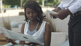 有黑发的好非裔美国人的女孩使用智能手机和采取命令在外部餐馆 免版税库存图片
