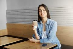有黑发的快乐的妇女在坐在自助食堂,饮料咖啡的时髦衣裳在长的天以后在工作,梦想 库存图片