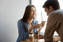 有黑发的快乐的美丽的女孩在咖啡馆坐日期,笑和辨别滑稽可笑的故事和生活到她 免版税图库摄影