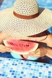 有黑发的性感的妇女吃西瓜的 库存图片
