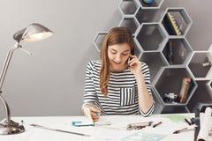 有黑发的悦目年轻企业家设计师在镶边衬衣谈话在有顾客谈论的电话 图库摄影
