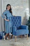 有黑发的美丽的女孩在一把蓝色扶手椅子附近站立 免版税图库摄影