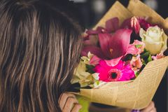 有黑发的美丽的女孩有花花束的从一个百合、大丁草、白玫瑰和德国锥脚形酒杯的在黑暗的背景 A 免版税库存照片